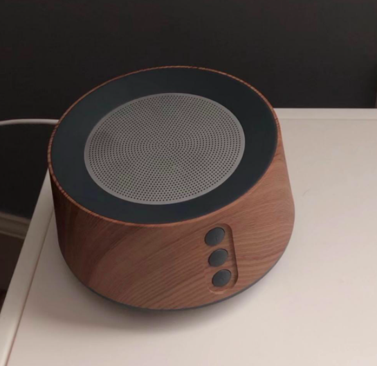 Reviewer photo showing white-noise machine in wood grain