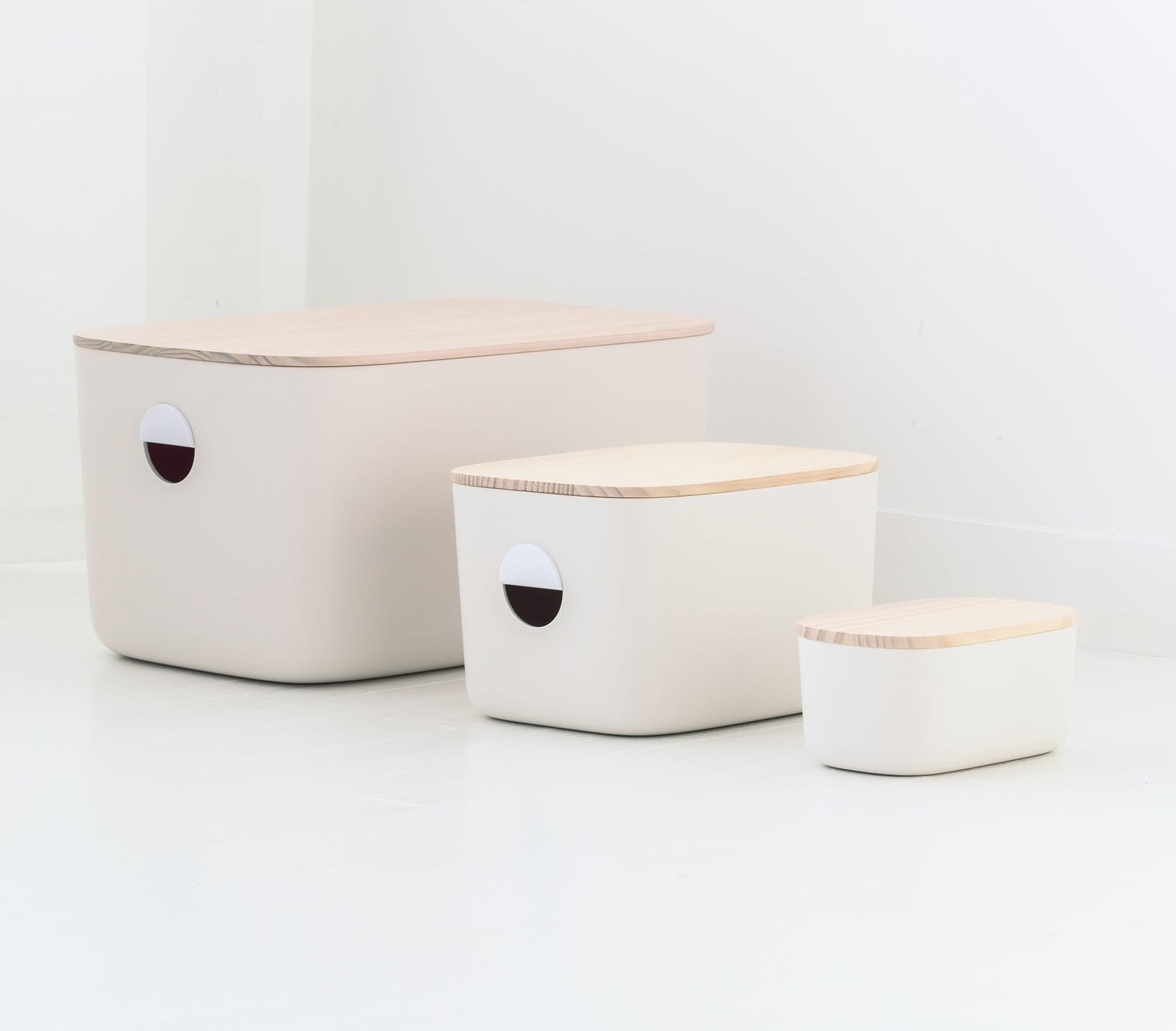 Three white bins with light wood tops in different sizes.