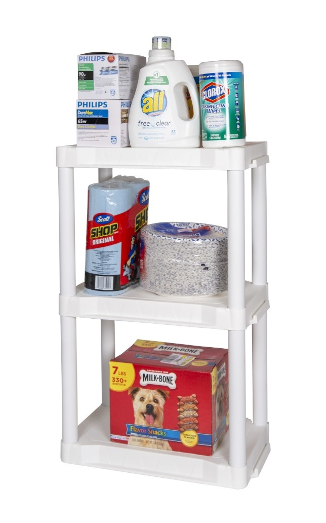 The white shelving unit being used to hold dog treats, plastic plates, and cleaning products