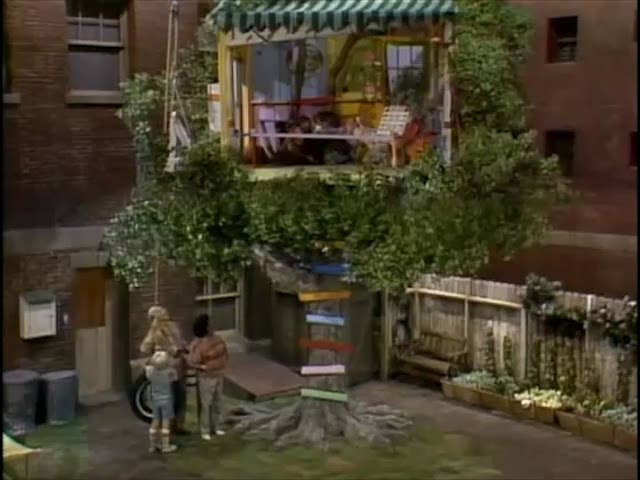A exterior shot of a tree with Punky's colorful tree house on top of it