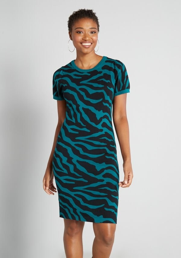 A model wearing the teal and black short-sleeve dress that hits above the knee