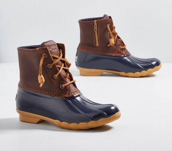 The brown leather and navy and tan rubber boots with leather laces and a side zip