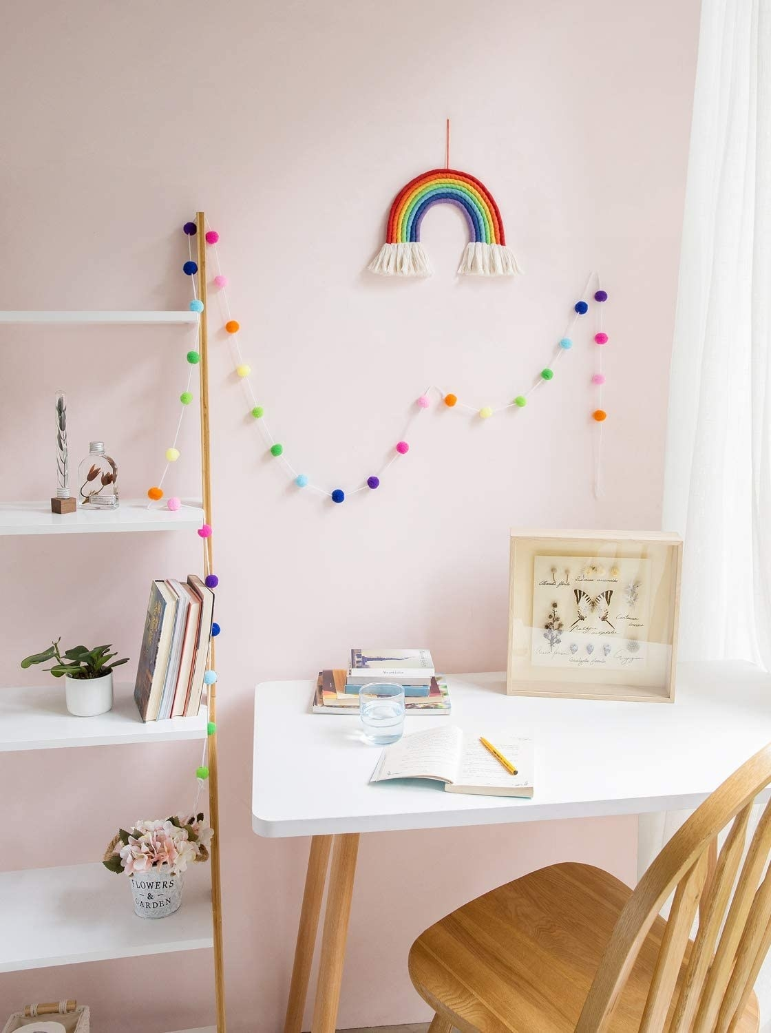 Rainbow colored pom pom garland and rainbow shaped wall hanging above desk