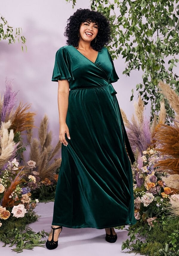 A model in the emerald short-sleeve dress with a tie waist and surplice neckline