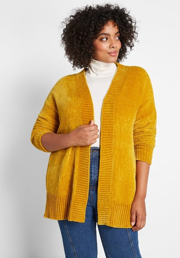 A model wearing the open gold cardigan that hits below the hips