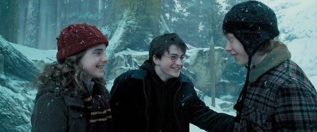 Hermione, Harry, and Ron laughing together in the snow