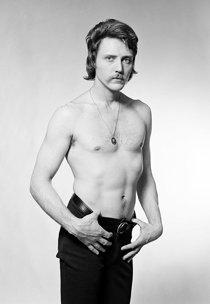 Shirtless in black and white with a mustache