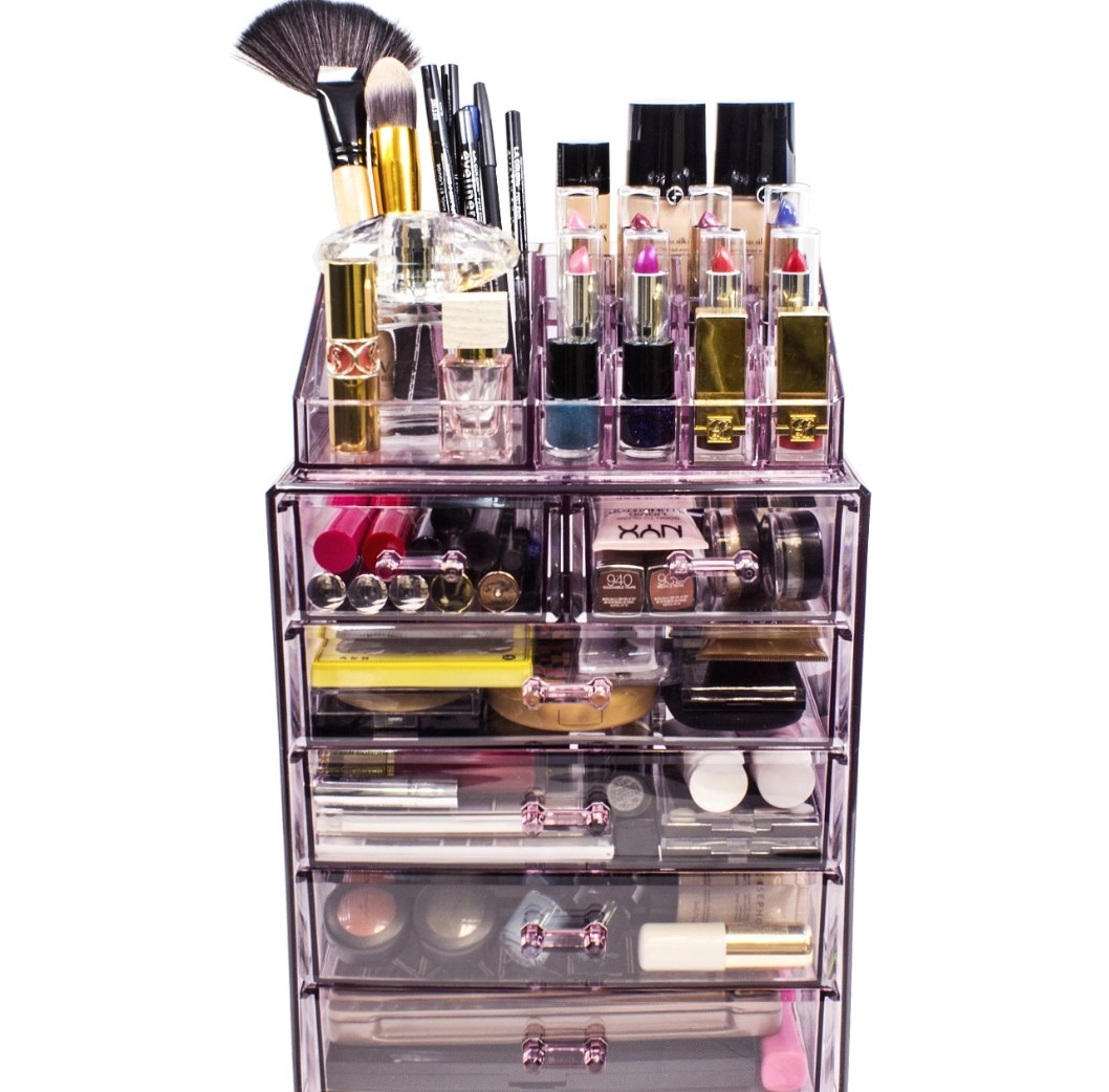The pink acrylic makeup organizer holding lipstick, brushes, and more