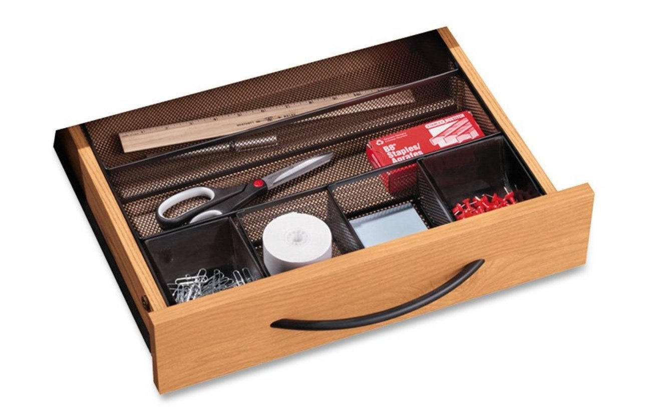 The drawer organizer being used to hold a ruler scissors and other office essentials