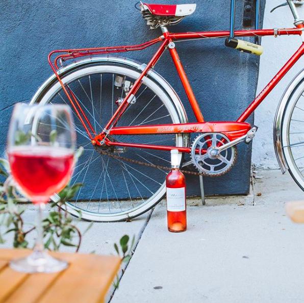 a bike outside with a bottle of rosé beside it