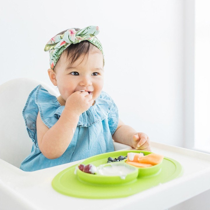 A child sitting a table with a 2-in-1 silicone plate and placemat stuck to the tray