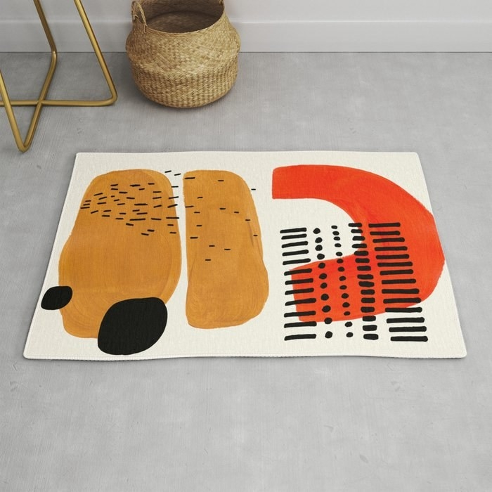 Rug in abstract shapes and white, black, red, and tan