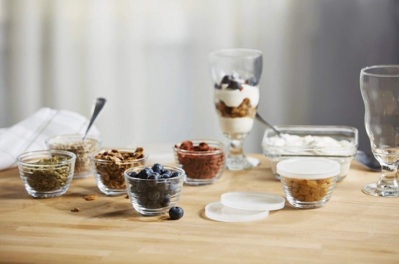The glass bowls being used to make a yogurt parfait