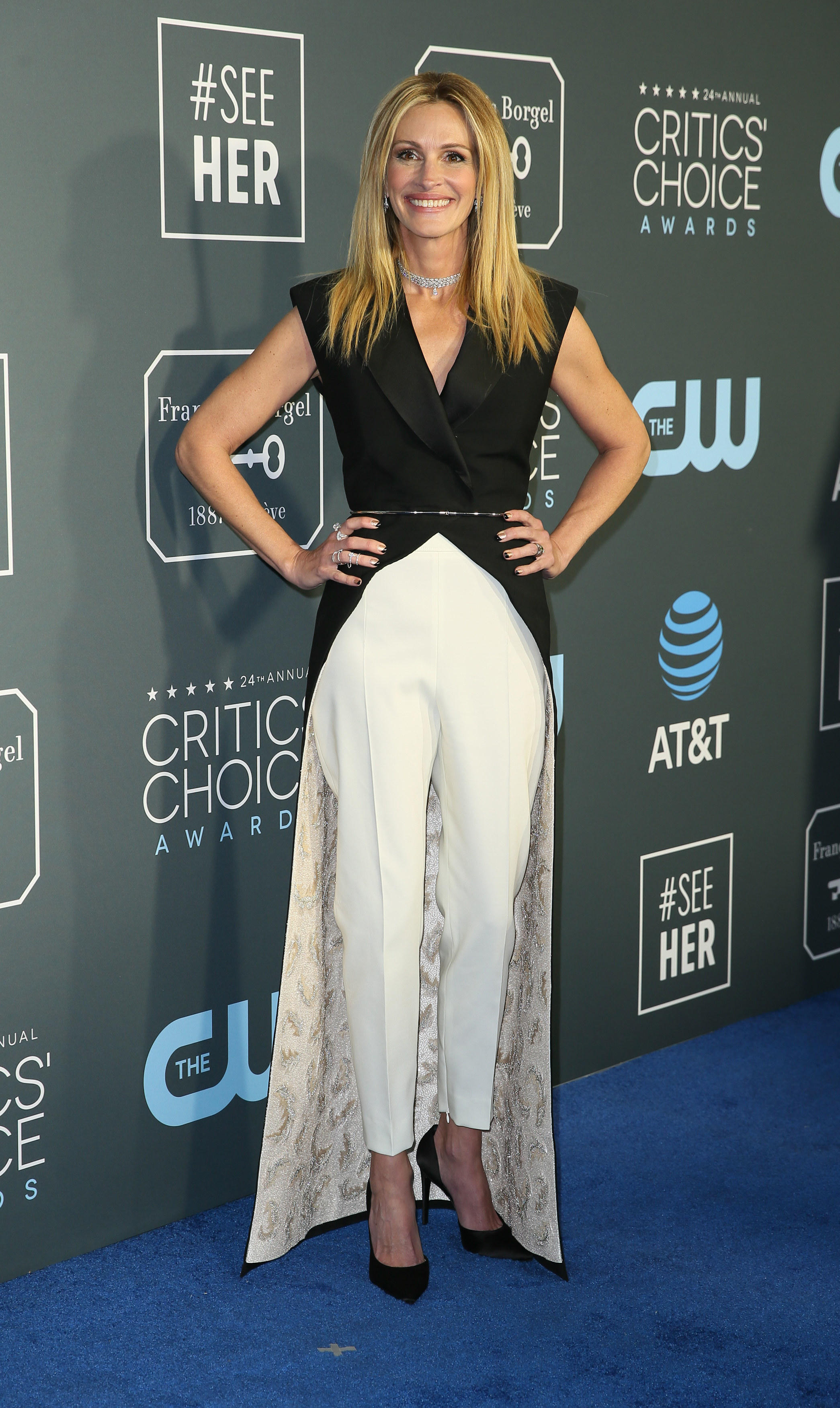 On a red carpet with hands on hips