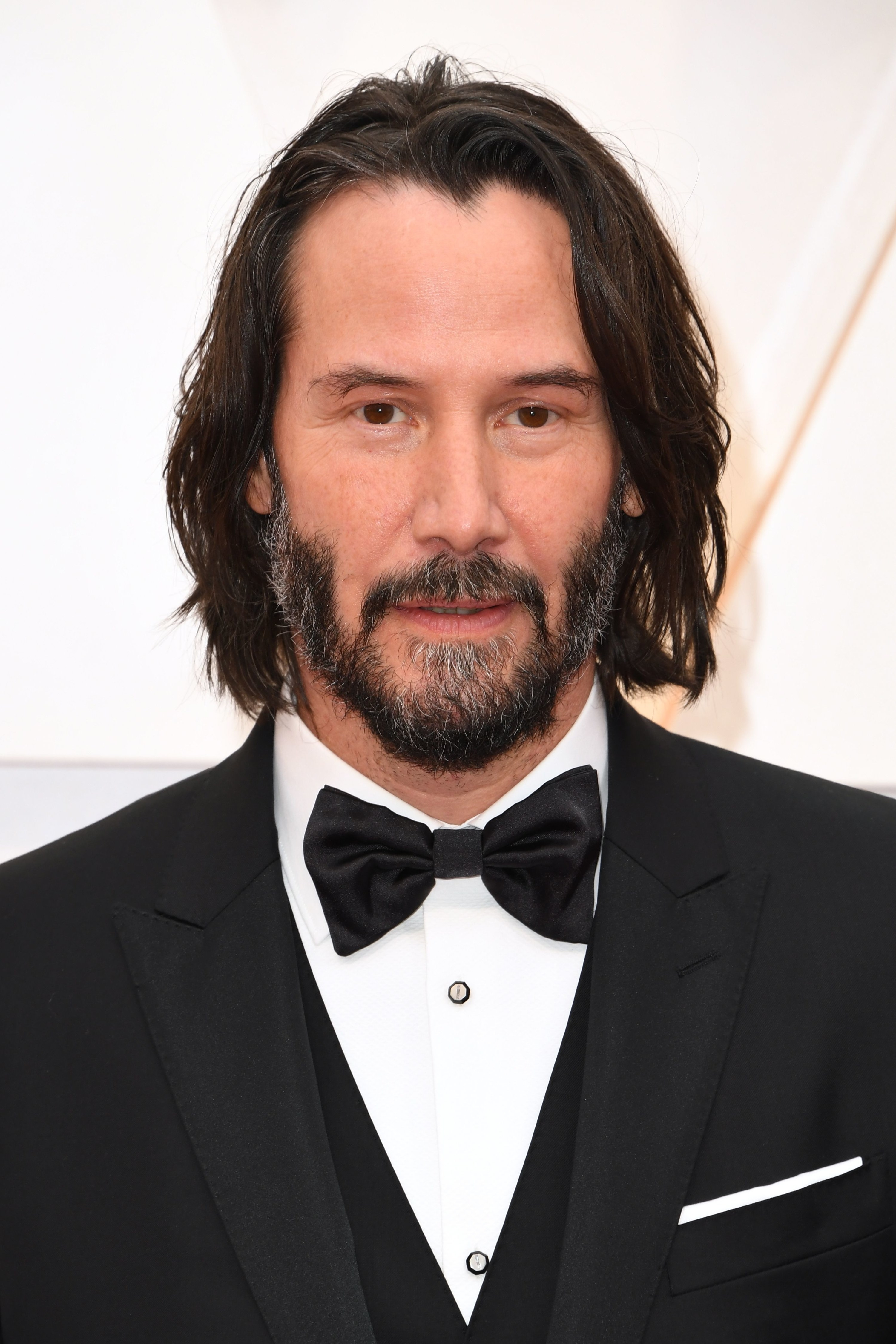 Gray beard, long hair, and black tie