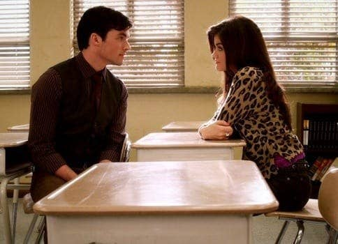 Ezra and Aria stare longingly at each other in a classroom