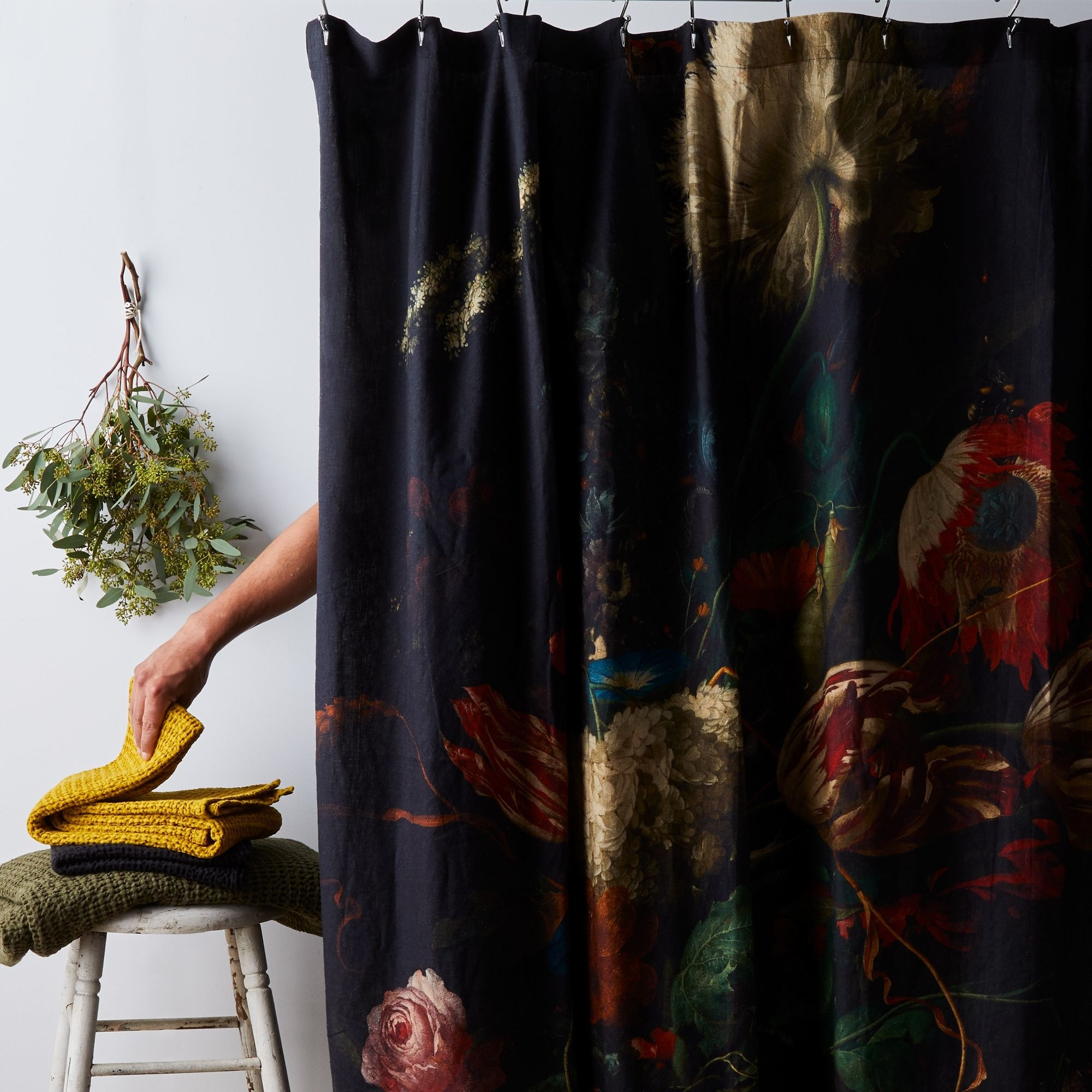 Black shower curtain with large painted flowers in various colors and shapes