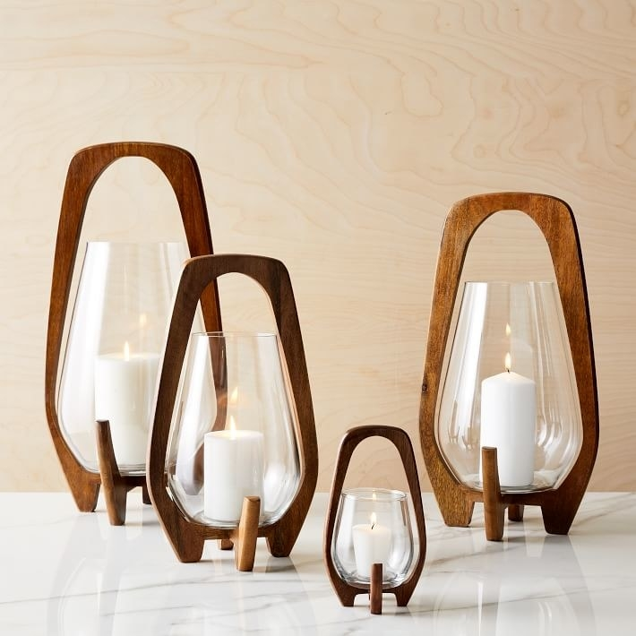 Four candles of different sizes in glass containers balanced on mid-century modern wooden frame
