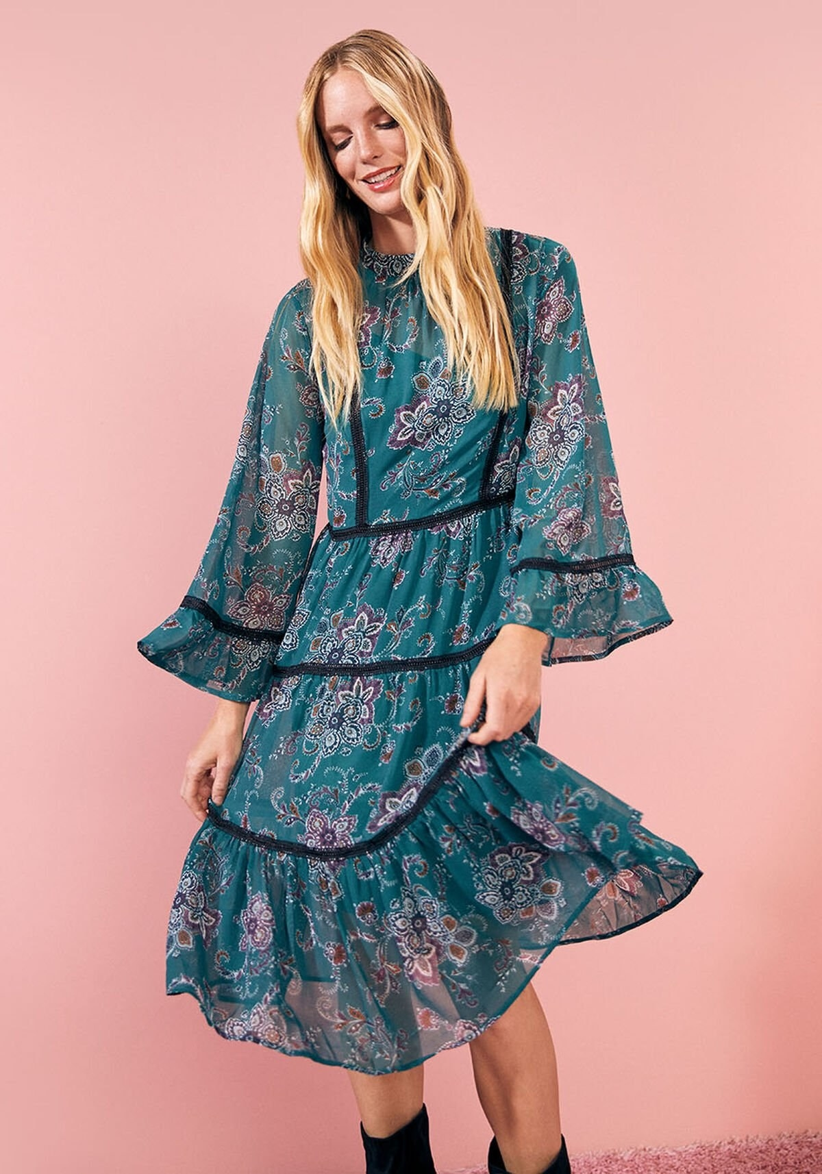 A model wears the loose midi dress with flowy bell sleeves and a tiered silhouette, made with green chiffon and a lace trim, that comes down to their knees