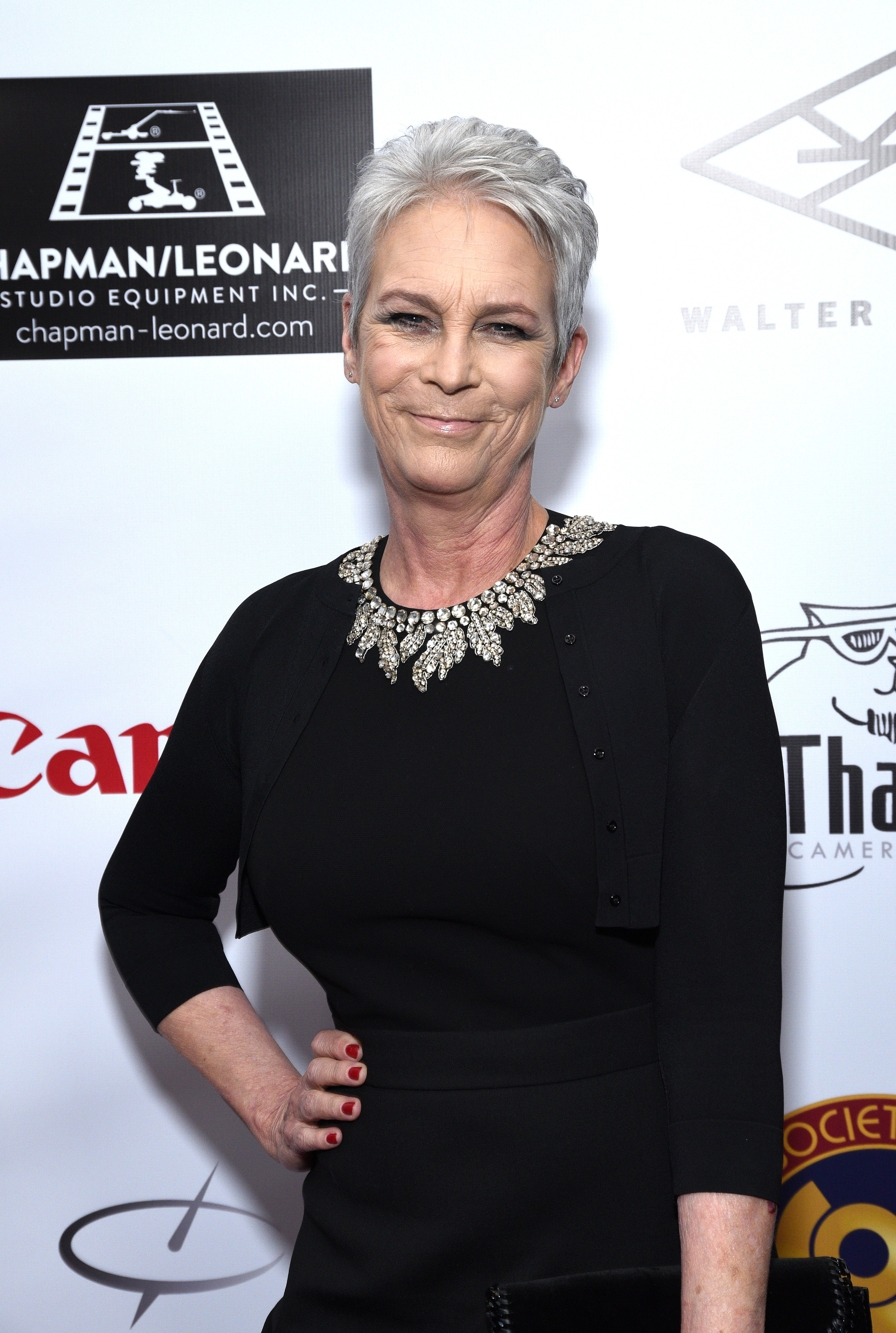 Smiling with gray hair and hands on hips on the red carpet