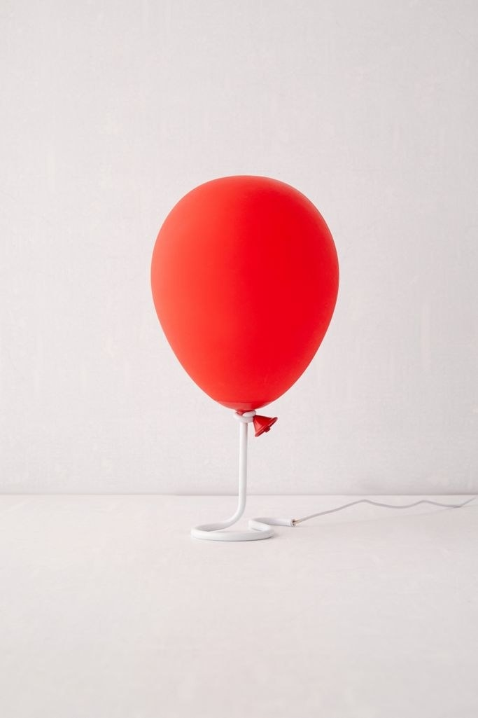 Red balloon lamp that appears to be hovering above table on white string