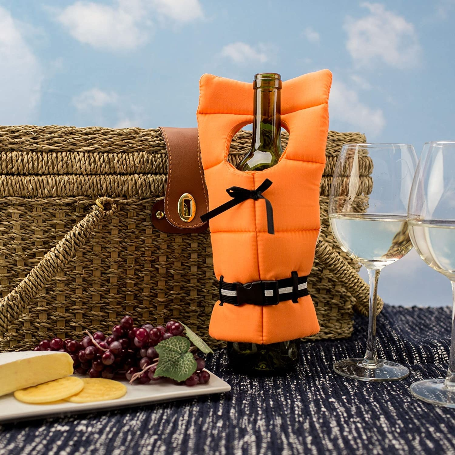 A bottle of wine with the lifejacket on it surrounded by a cheese plate, wine glasses, and picnic basket.