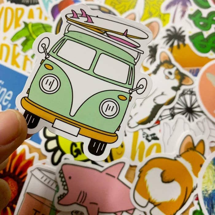 A person holding a vintage van sticker