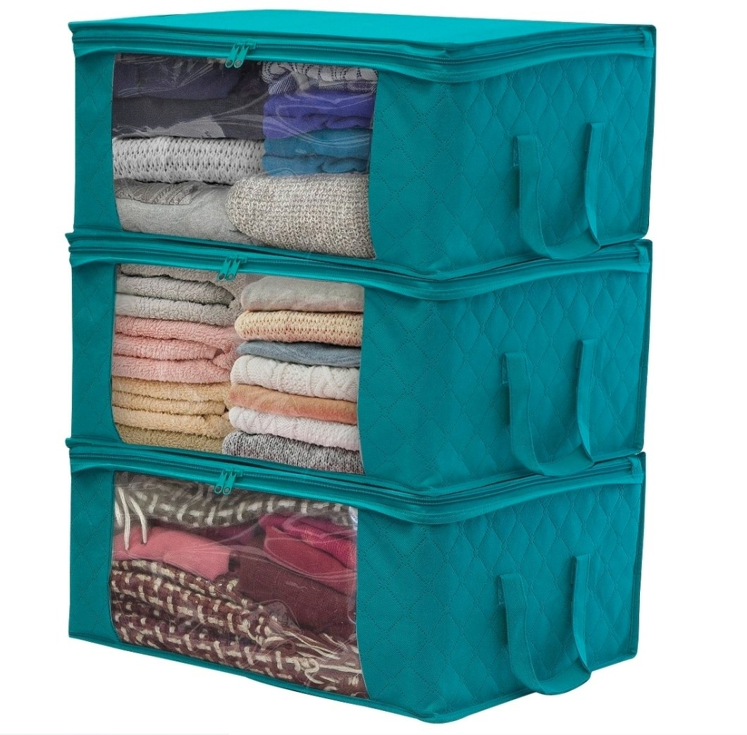 The foldable storage bag in blue being used to hold folded clothes
