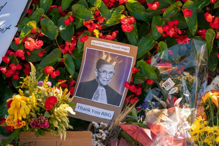 "A photo of Ginsburg wearing a crown with the words ""Thank You RBG"" on it rests amid flowers"