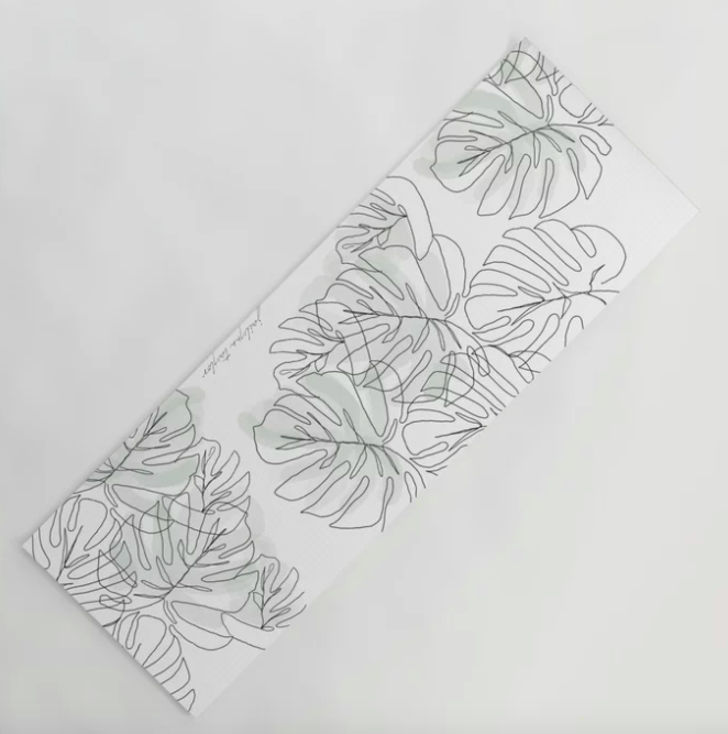 White yoga mat with a gray and black botanical leaf print