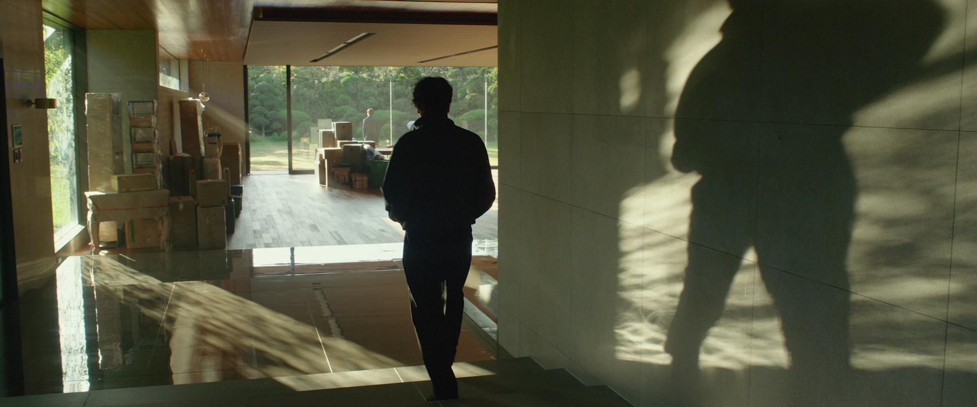 Ki Taek stands in the house looking out at Ki Woo