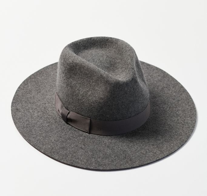 The panama hat or elongated flat-brimmed fedora in gray with a bow around the dimpled crown to hide the adjustable strap