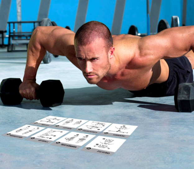 Model goes into push-up position with weights in front of a stack of exercise cards