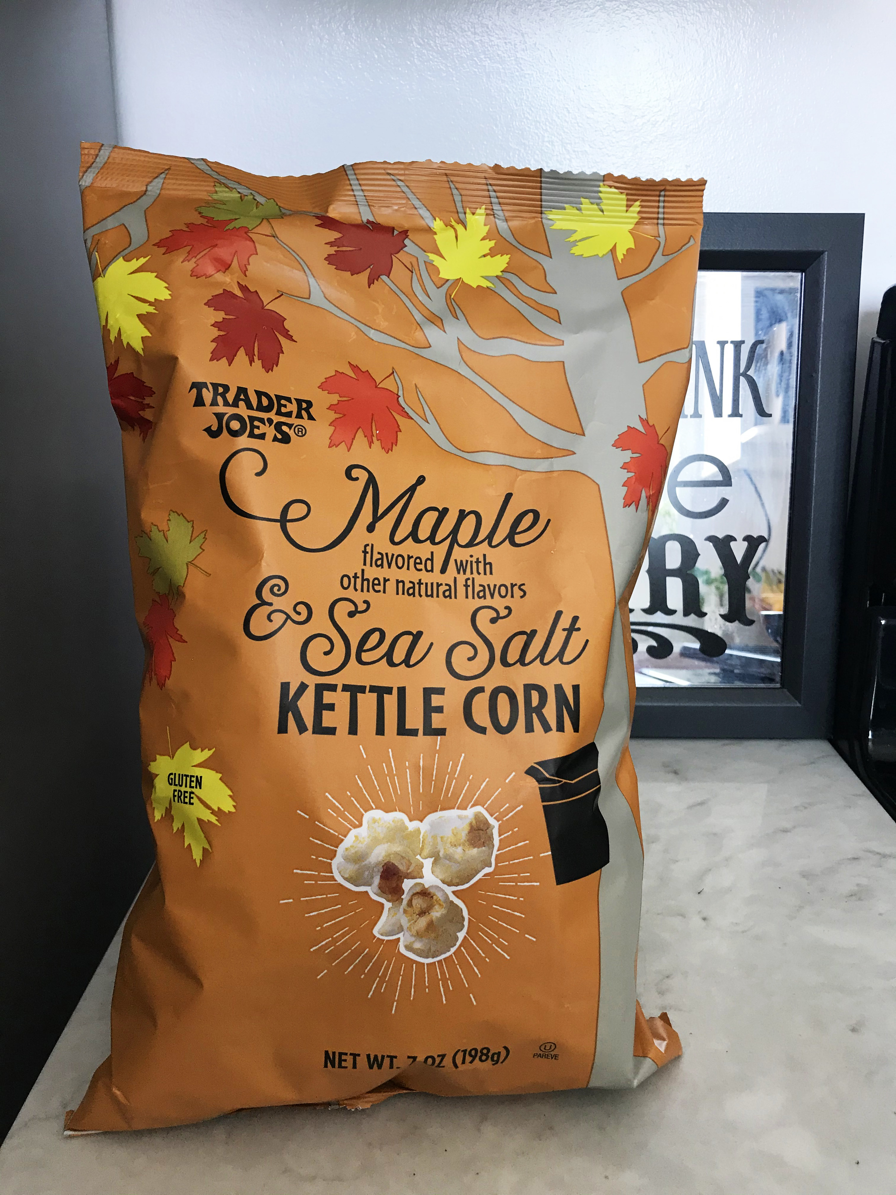 A bag of kettle corn sits upright on a marble counter