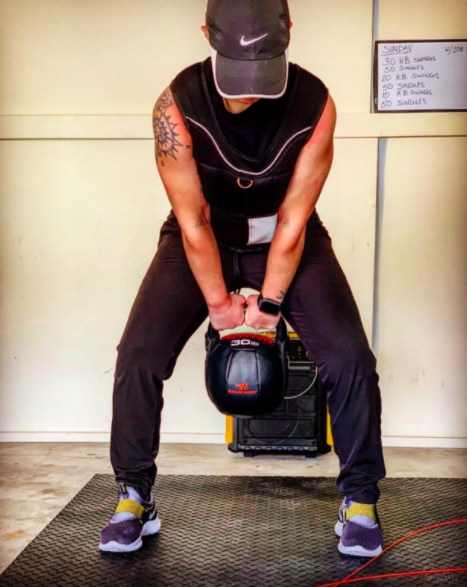 Reviewer squats with 30-pound black kettlebell in their home gym