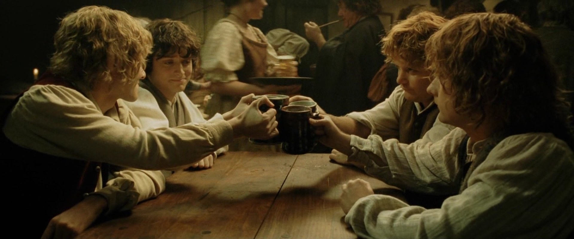 Frodo, Sam, and others cheers at the pub