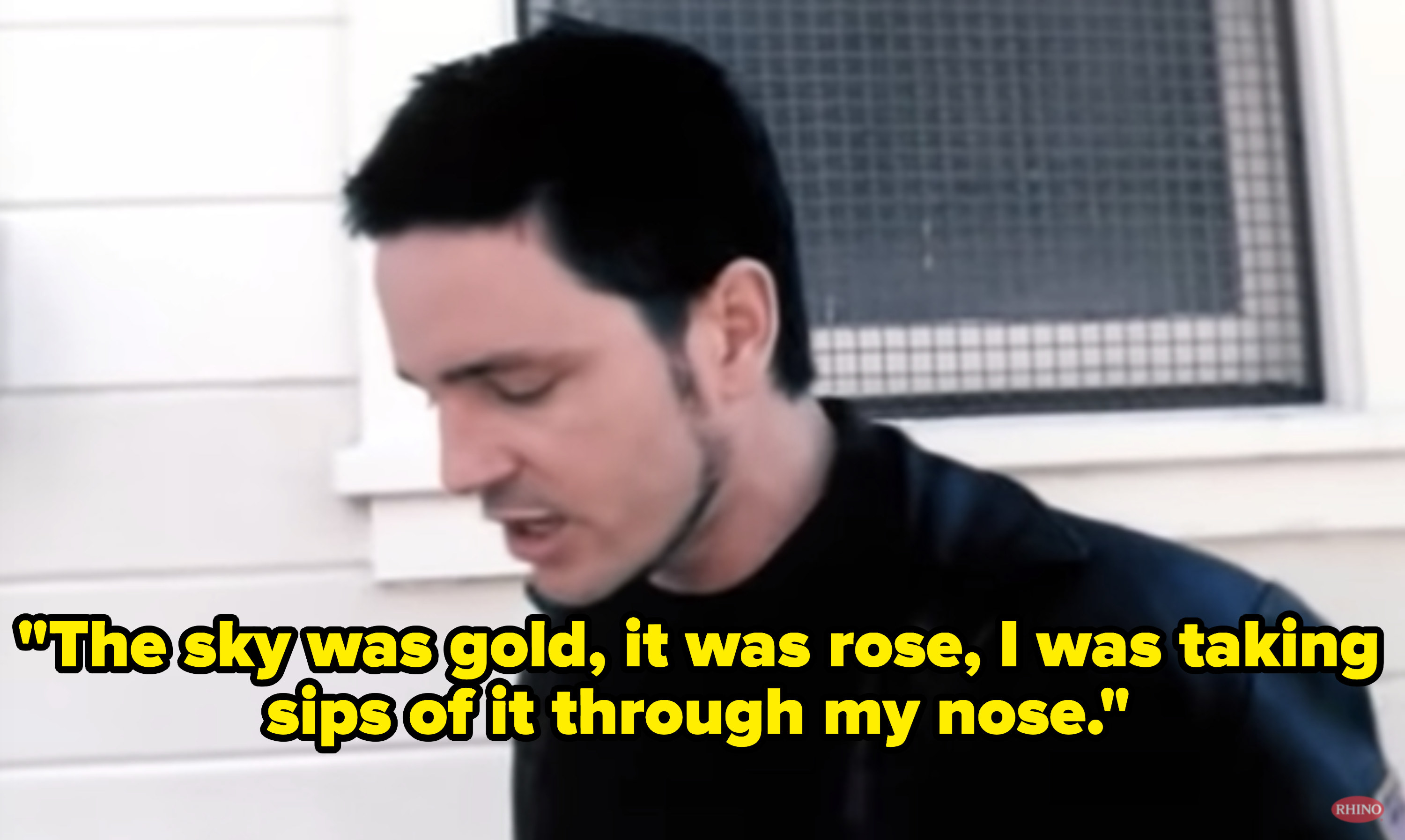 Stephen singing outside a house.
