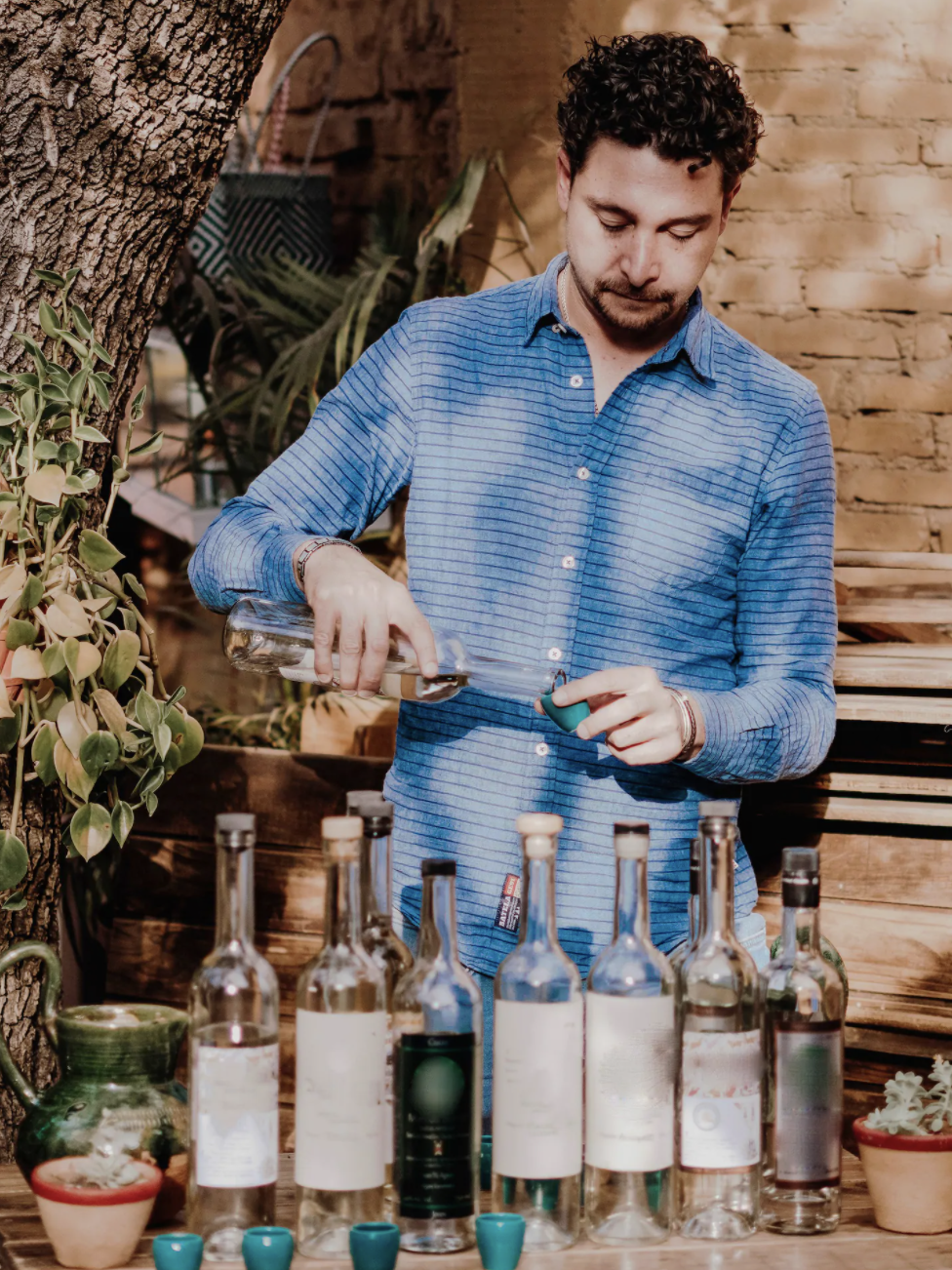 A man in a button up pours mezcal into a shot class with multiple, half-empty bottles sit before him