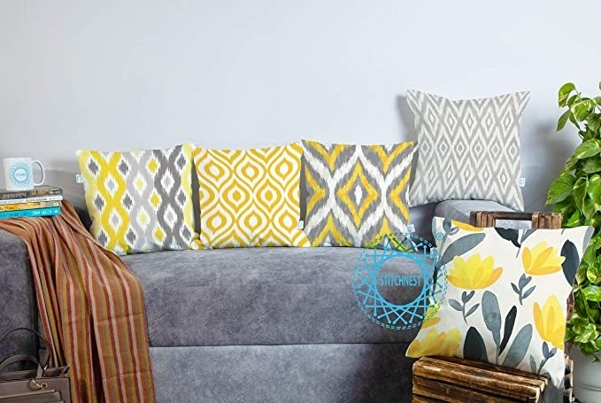 A sofa with the grey and yellow cushions on it, in various floral and geometric patterns.