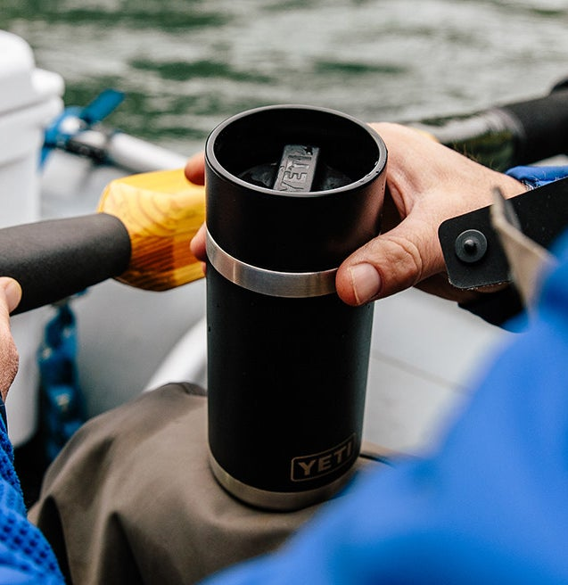 A person holding the rambler cup on a boat