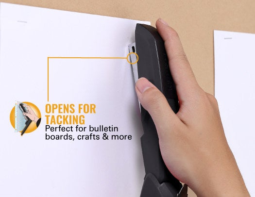 Person using the open design on the stapler to staple paper against a bulletin board
