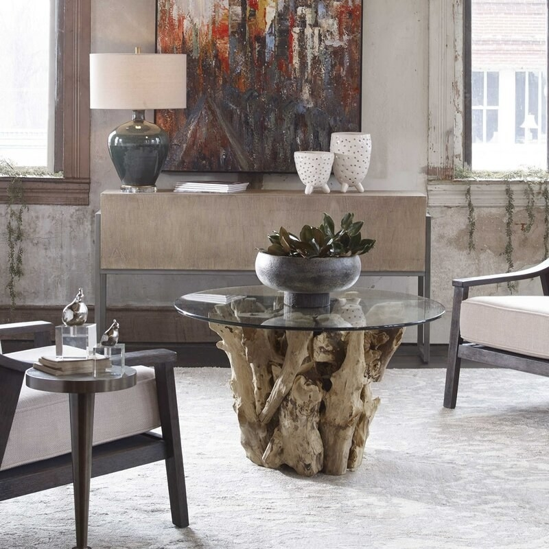 The glass-top coffee table, which has a base made of driftwood