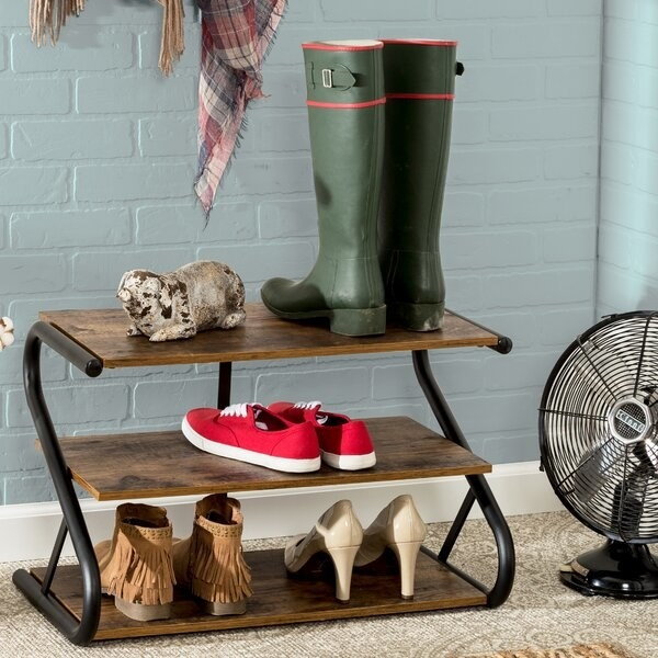 """Dark wood shoe rack with pipe sides in """"S"""" shape"""