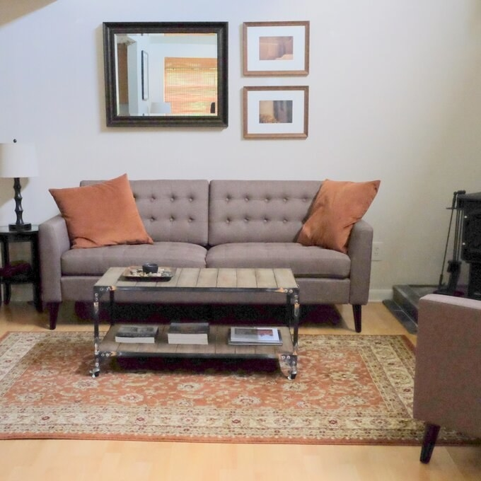 A reviewer's photo of the button-tufted sofa with dark brown legs in grey