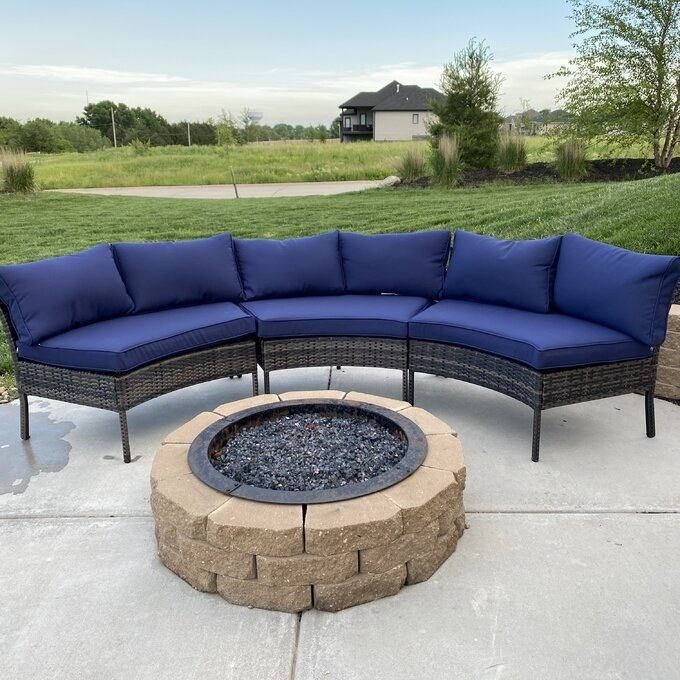 A reviewer's photo of the sectional with navy cushions and dark wicker base wrapped around a stone fire pit
