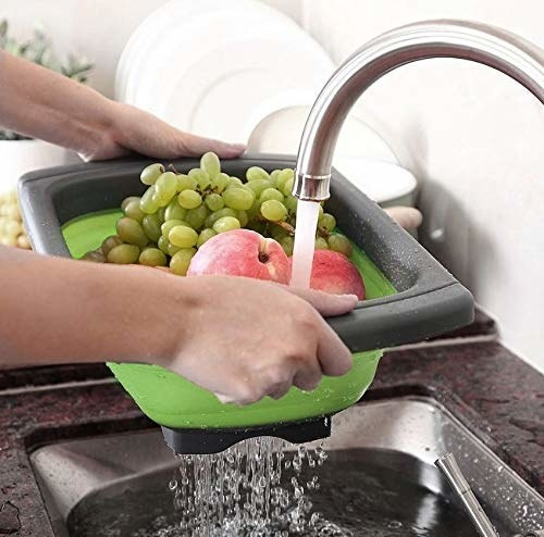 Person washing some grapes and apples in the colander.
