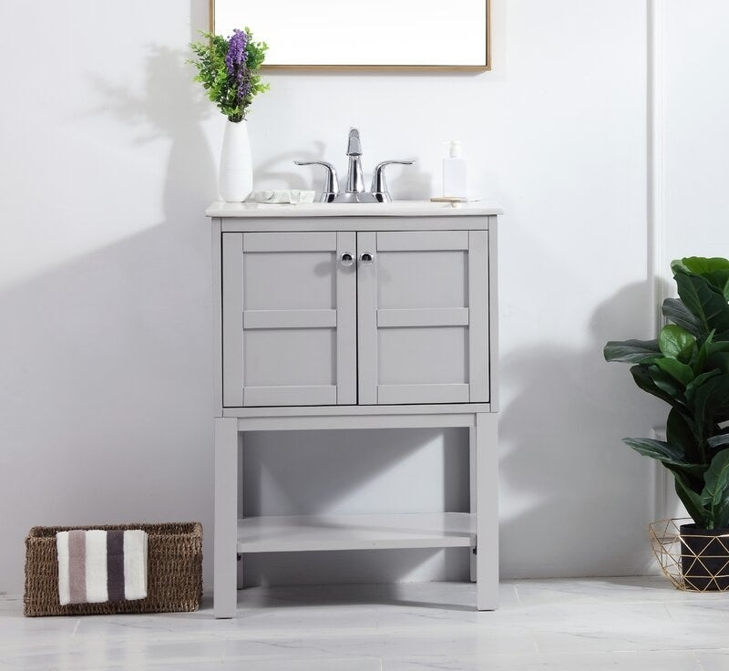 The grey vanity with white counter and a cabinet bottom, plus storage shelf below the cabinet doors