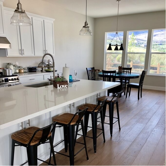 Reviewer's photo of the black metal stools with wood grain seat tucked under a kitchen counter