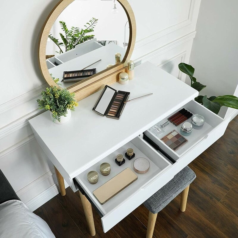 The vanity in white with wooden legs, two drawers, and a wooden mirror that attaches to the back