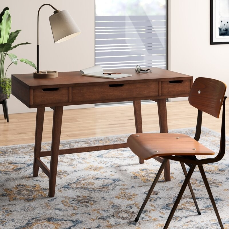 Mid-century modern style desk with three drawers under the top surface